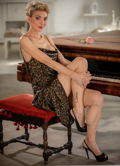 Super fit blonde MILF Natalie Anna sits naked at her piano.