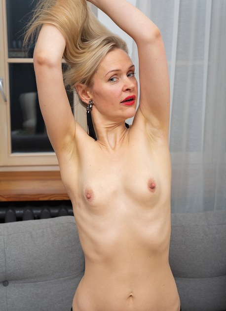 Small breasted blonde MILF Midge Mayor naked on the couch.